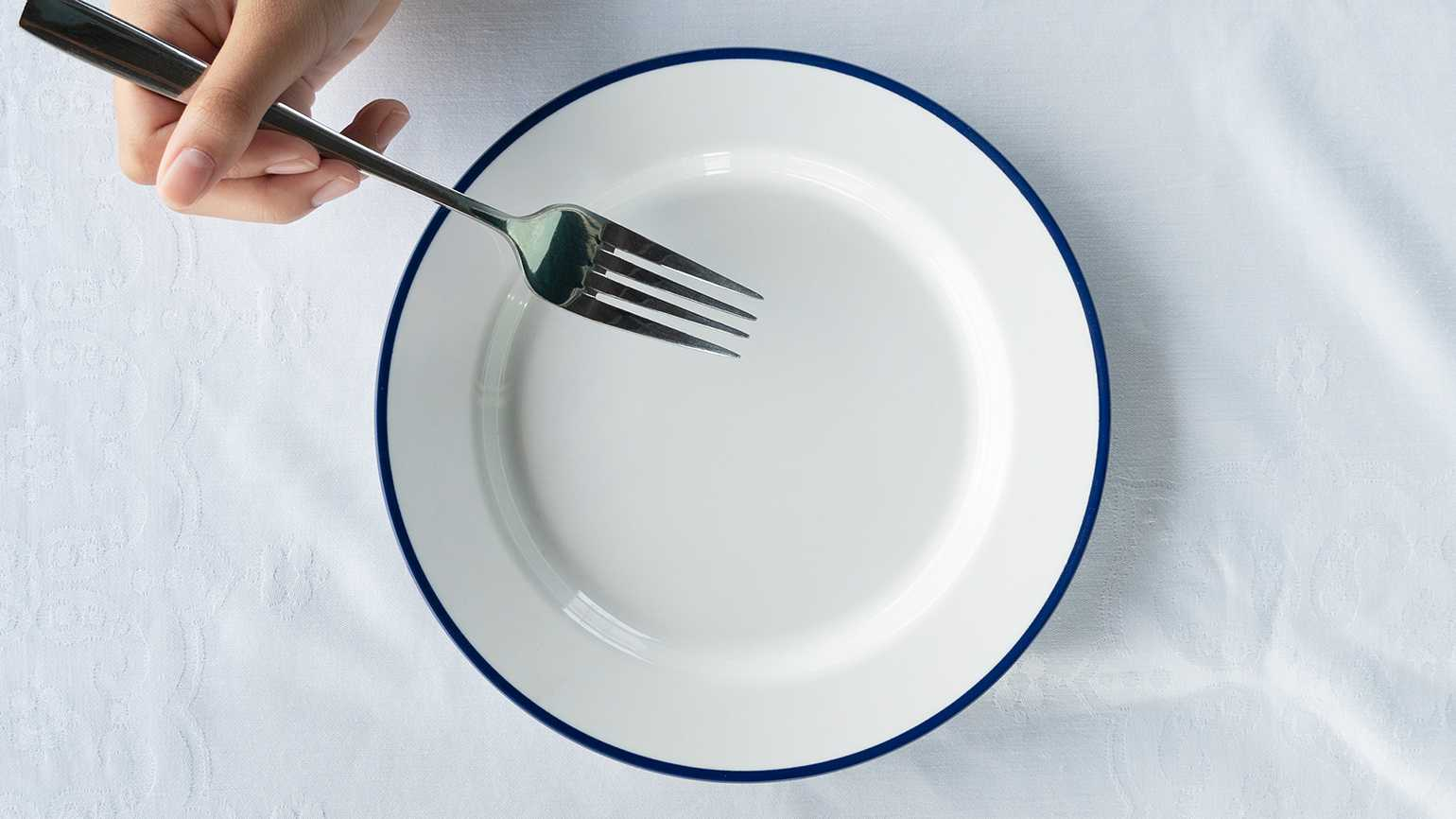 The hand of a woman diner clasps a fork