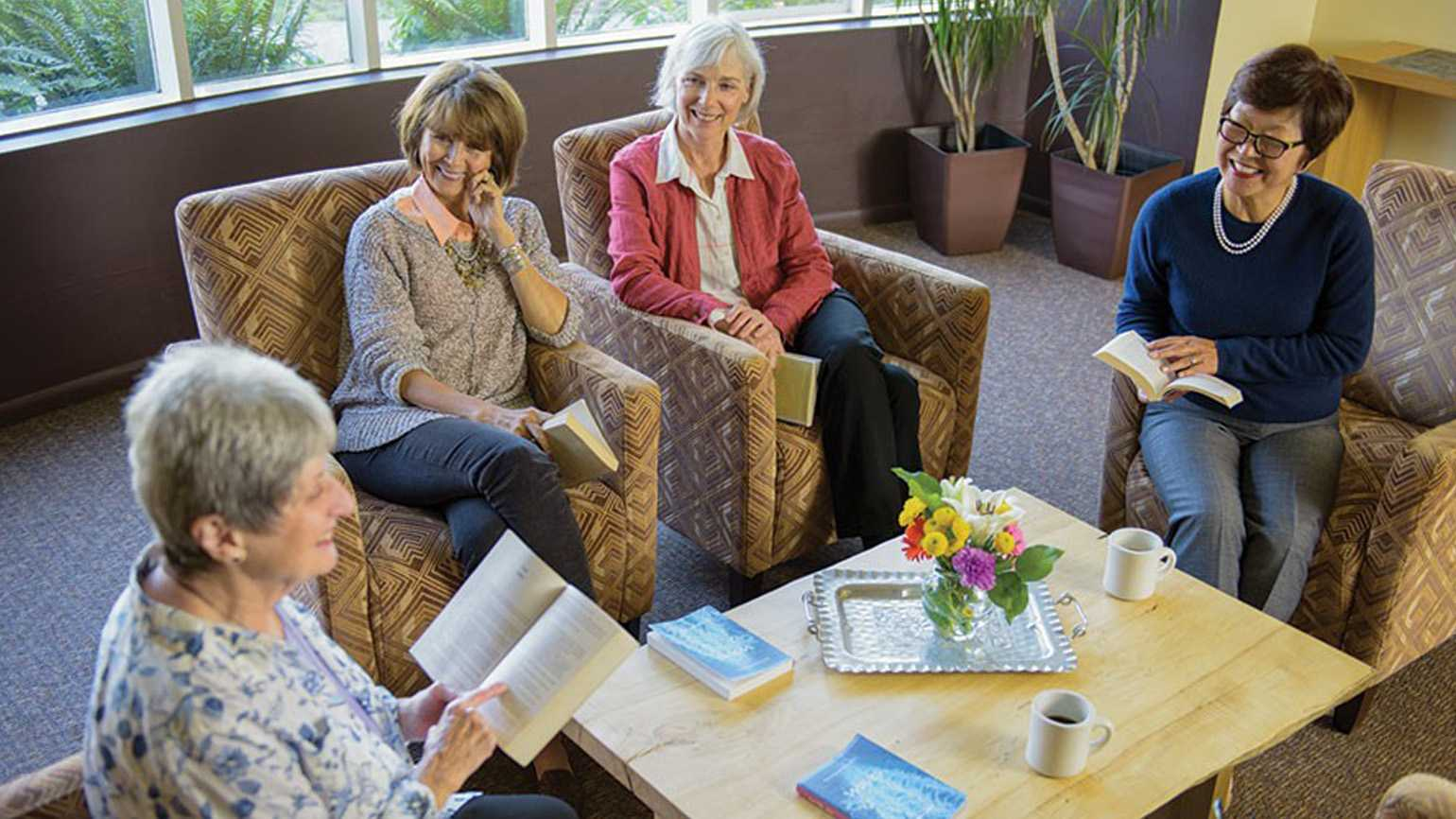A group of retirees reading together in a circle.