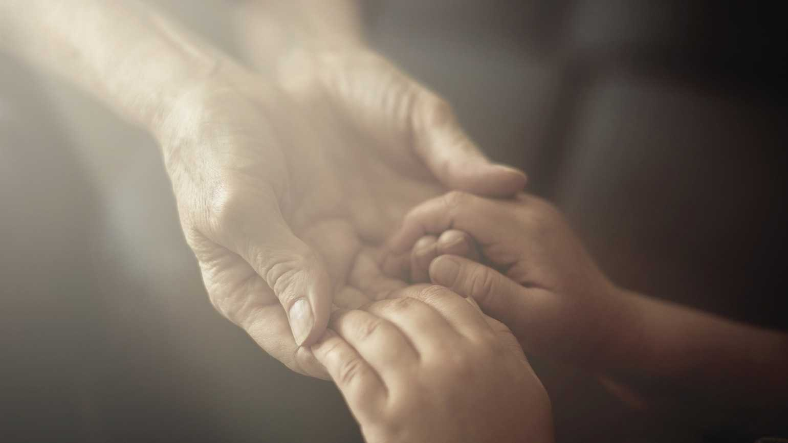 Grandson holding grandmother hands close up view (Getty Images)