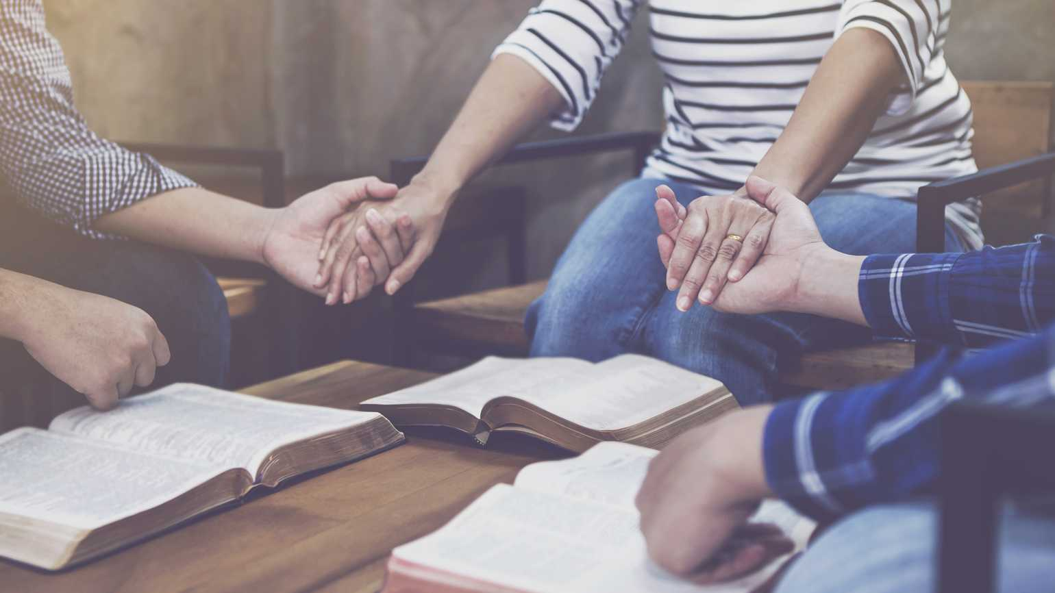 A group holding hands in prayer.