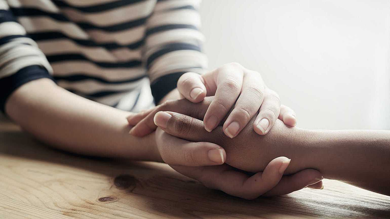 A woman comforts a grieving friend