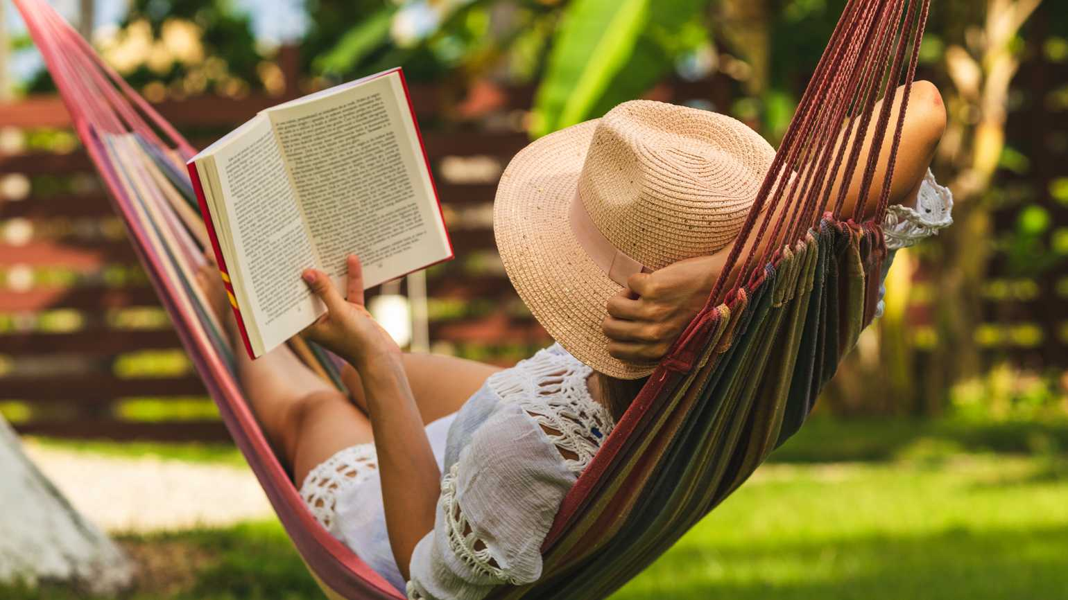 A woman reading a book in a hammock.