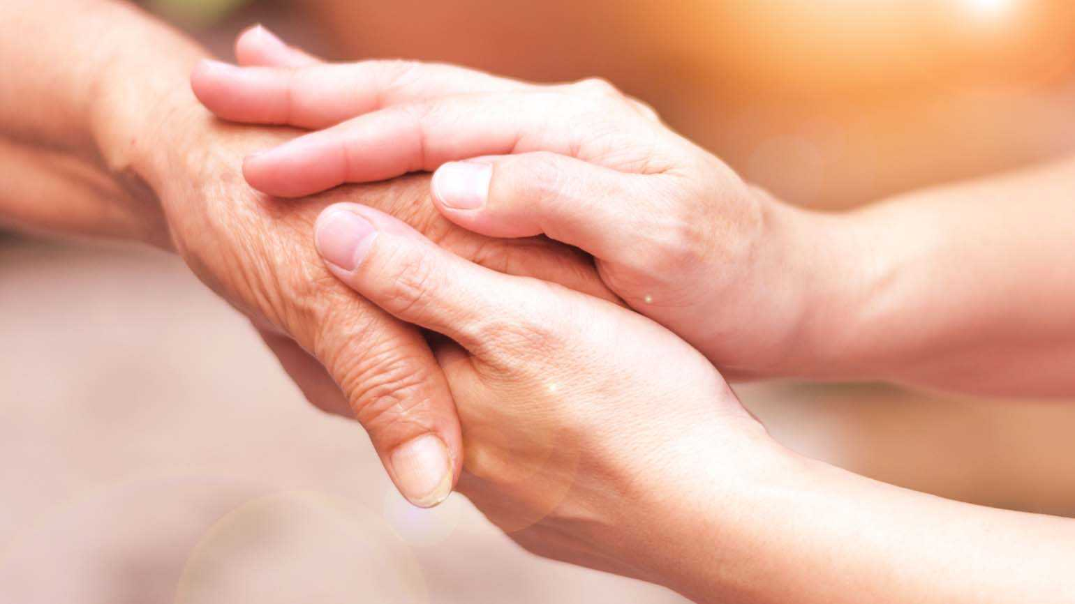 A pair of hands holding each other; Getty Images
