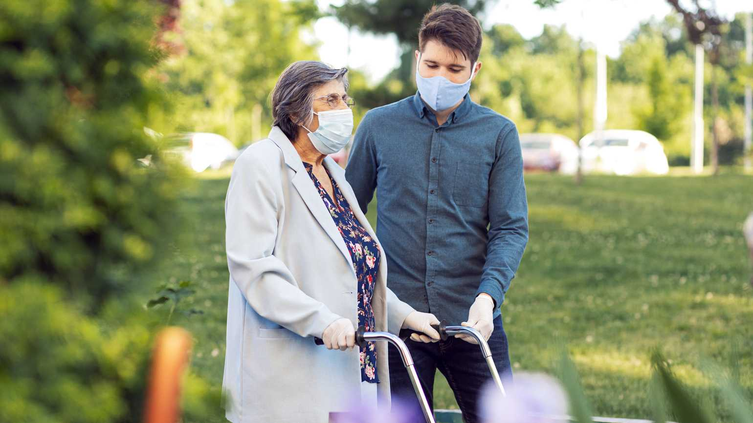 A young man helping an older woman wearing protective face masks; Getty Images