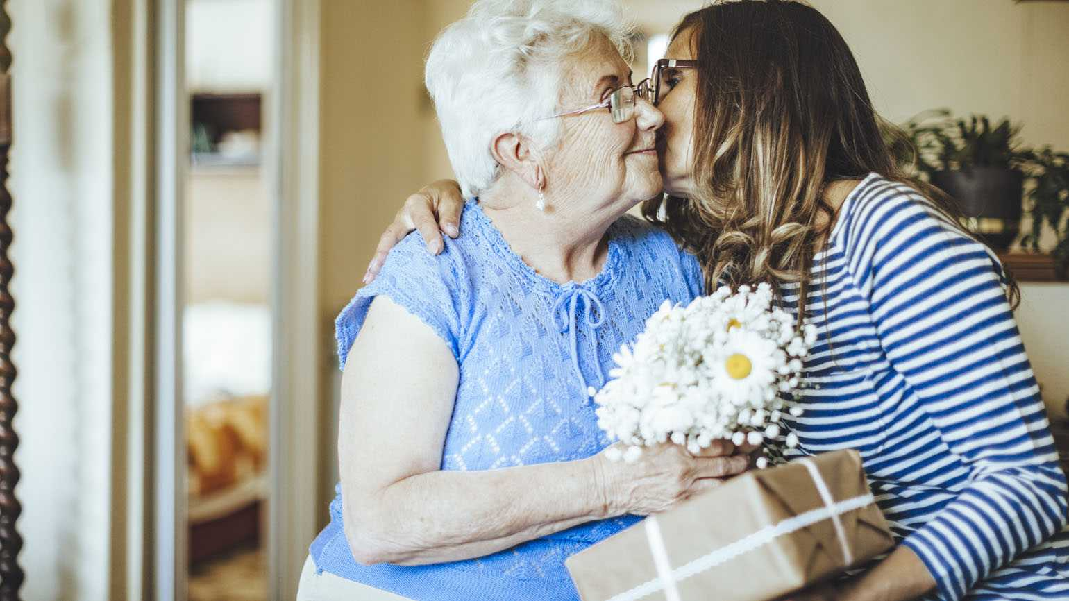 Senior woman is celebrating a joyful Mother's day moment with her daughter; Getty Images