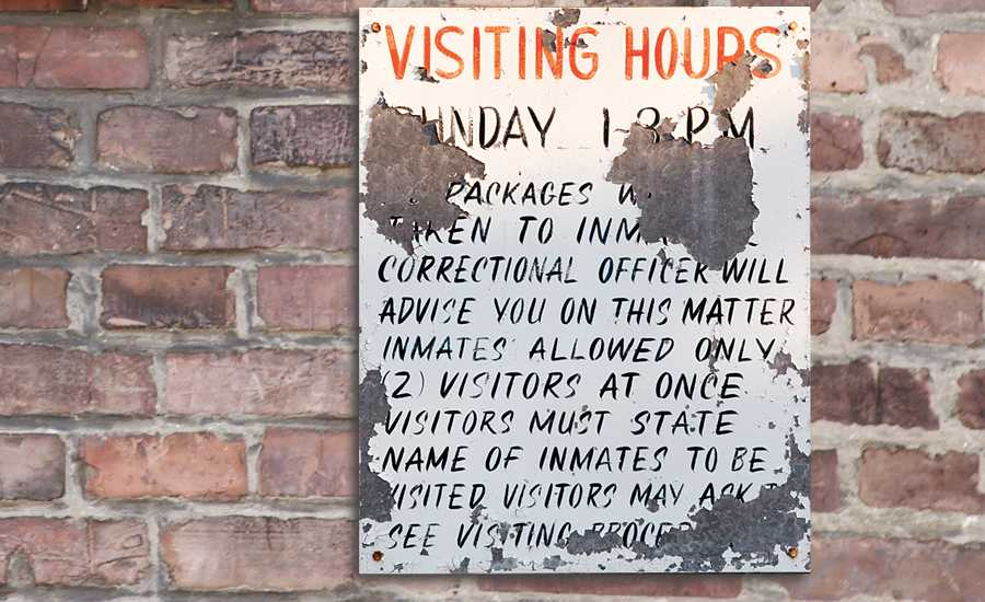 A sign listing visitor rules in a prison
