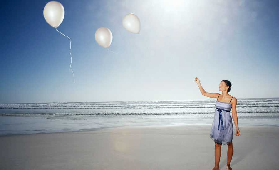A smiling woman sets free a trio of white balloons on a sun-drenched beach