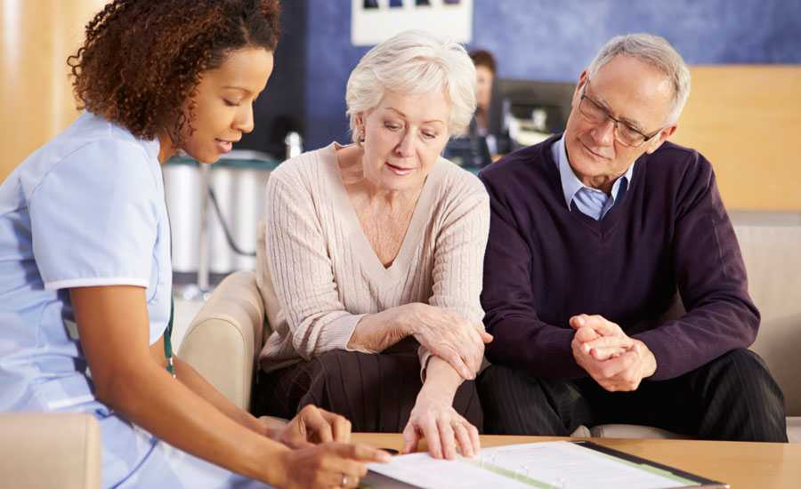 A mature couple reviews Medicare documents with a health practitioner