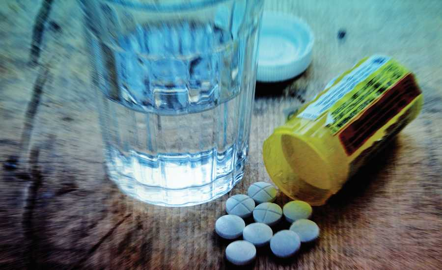 An open bottle of white pills and a glass a water, representing Roberta's plans for suicide