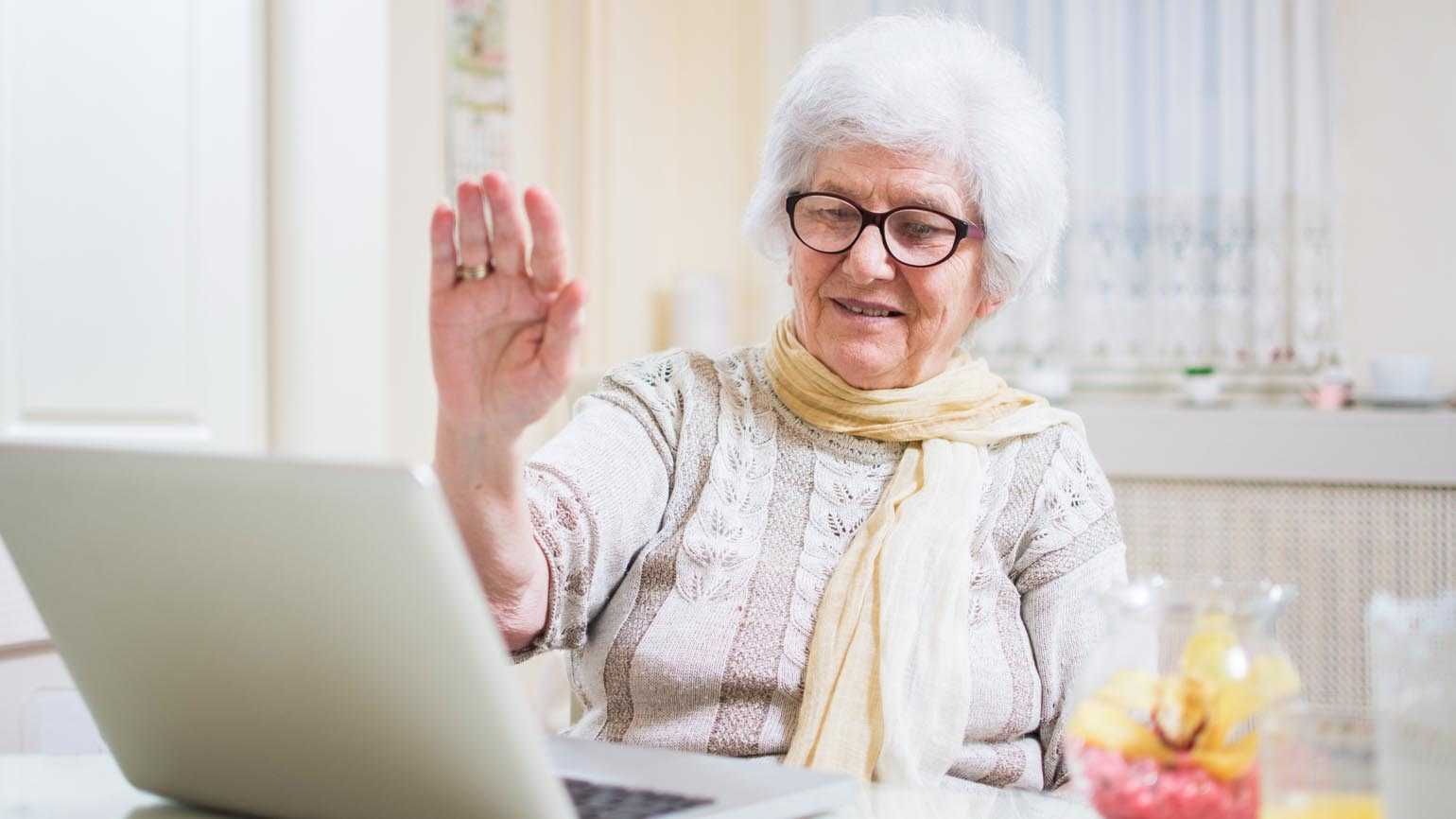 An elderly woman uses her laptip to video chat relatives.