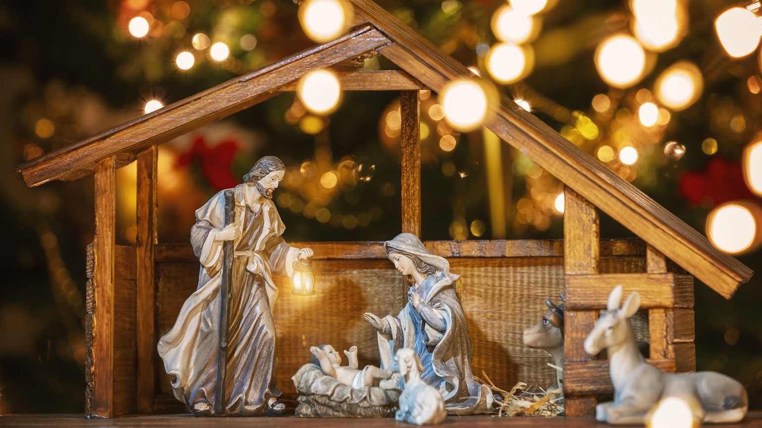 Christmas Manger scene with figurines including Jesus, Mary, Joseph and sheep.