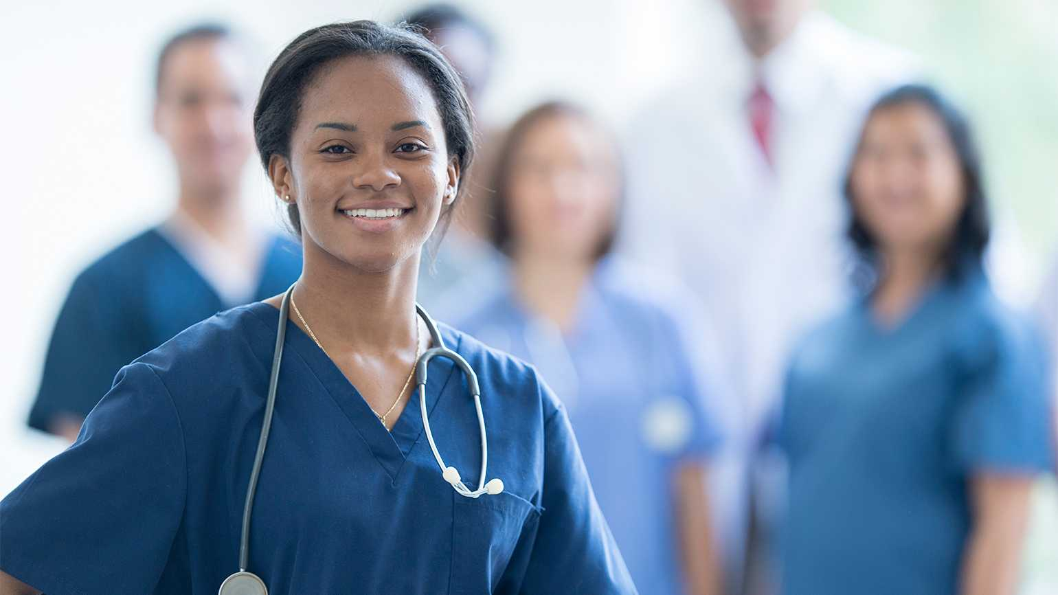 A nurse stands, smiling, as her colleagues look on