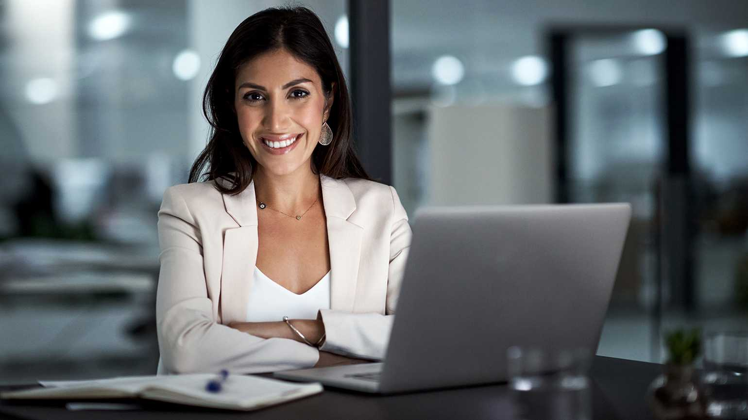 A woman who works in an office looks up from her computer with a smile