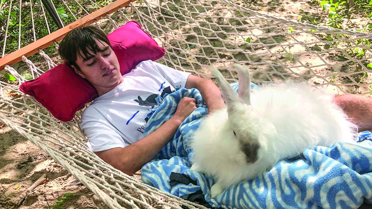 Caleb Smith relaxing on a hammock with a bunny