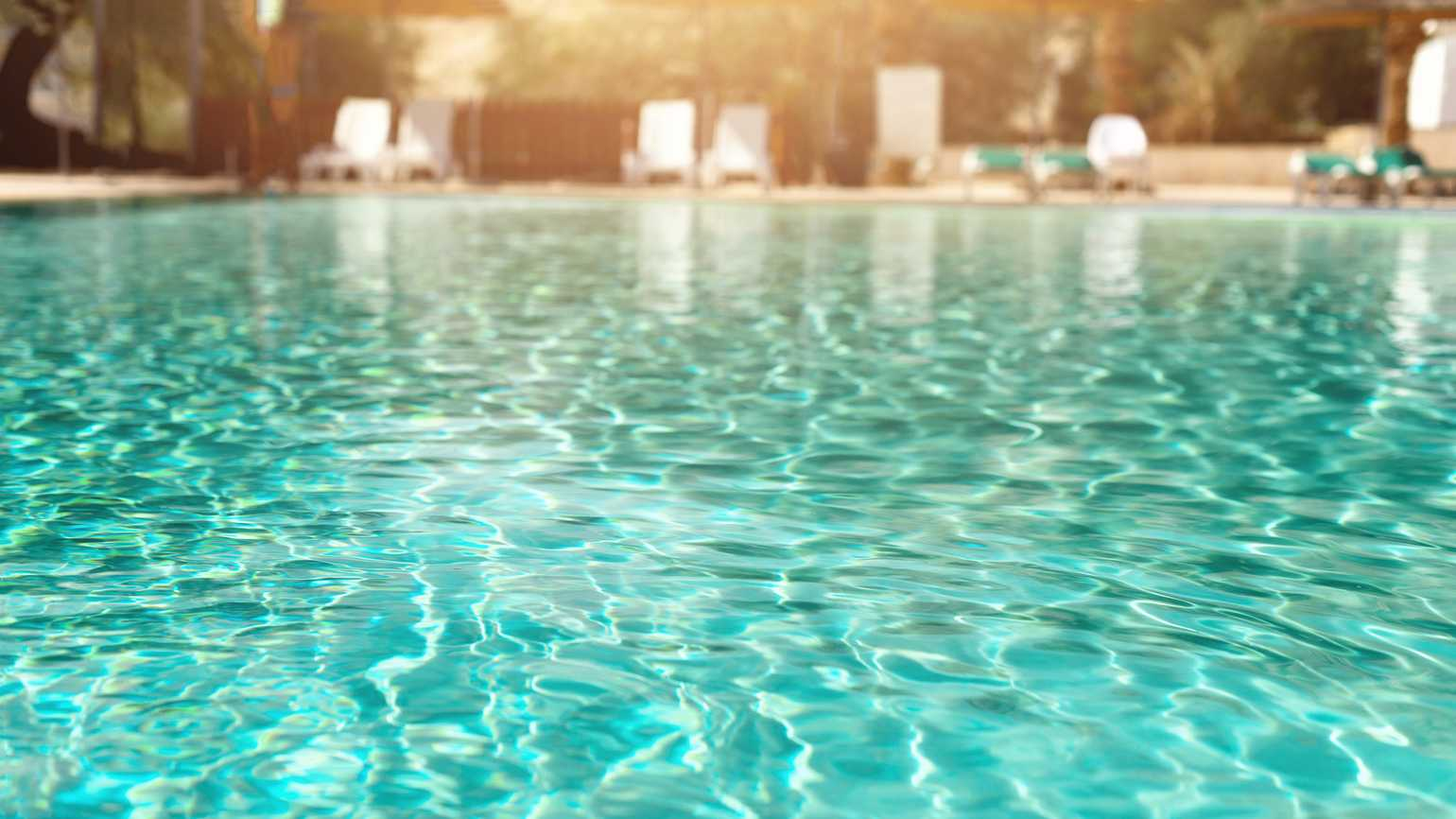 A close up of a pool as chair line the poolside.
