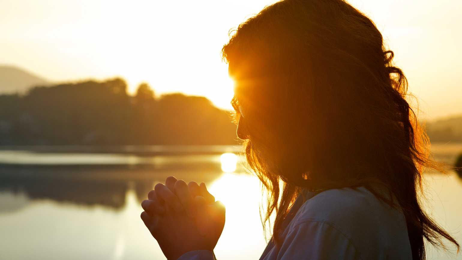 Woman praying by lake at sunrise.