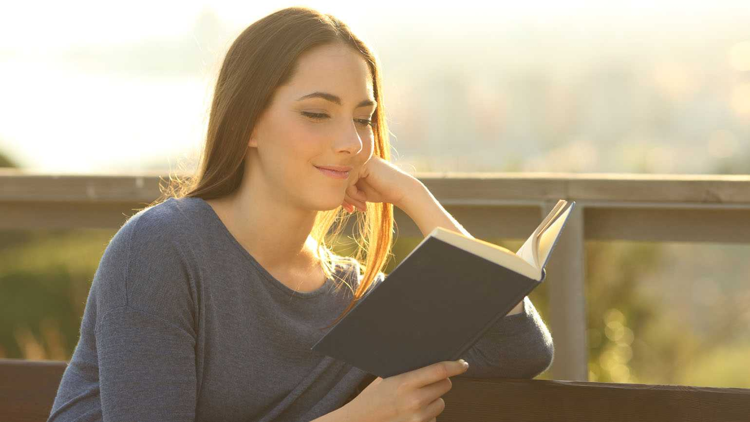 A woman reading outside; Getty Images