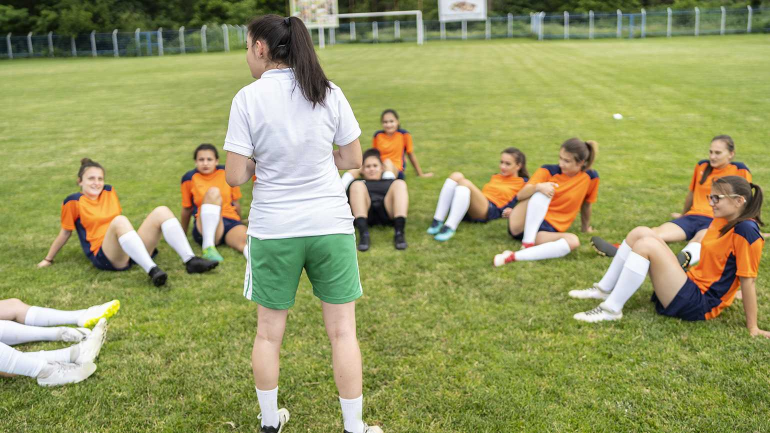 A coach addresses the players on her soccer team