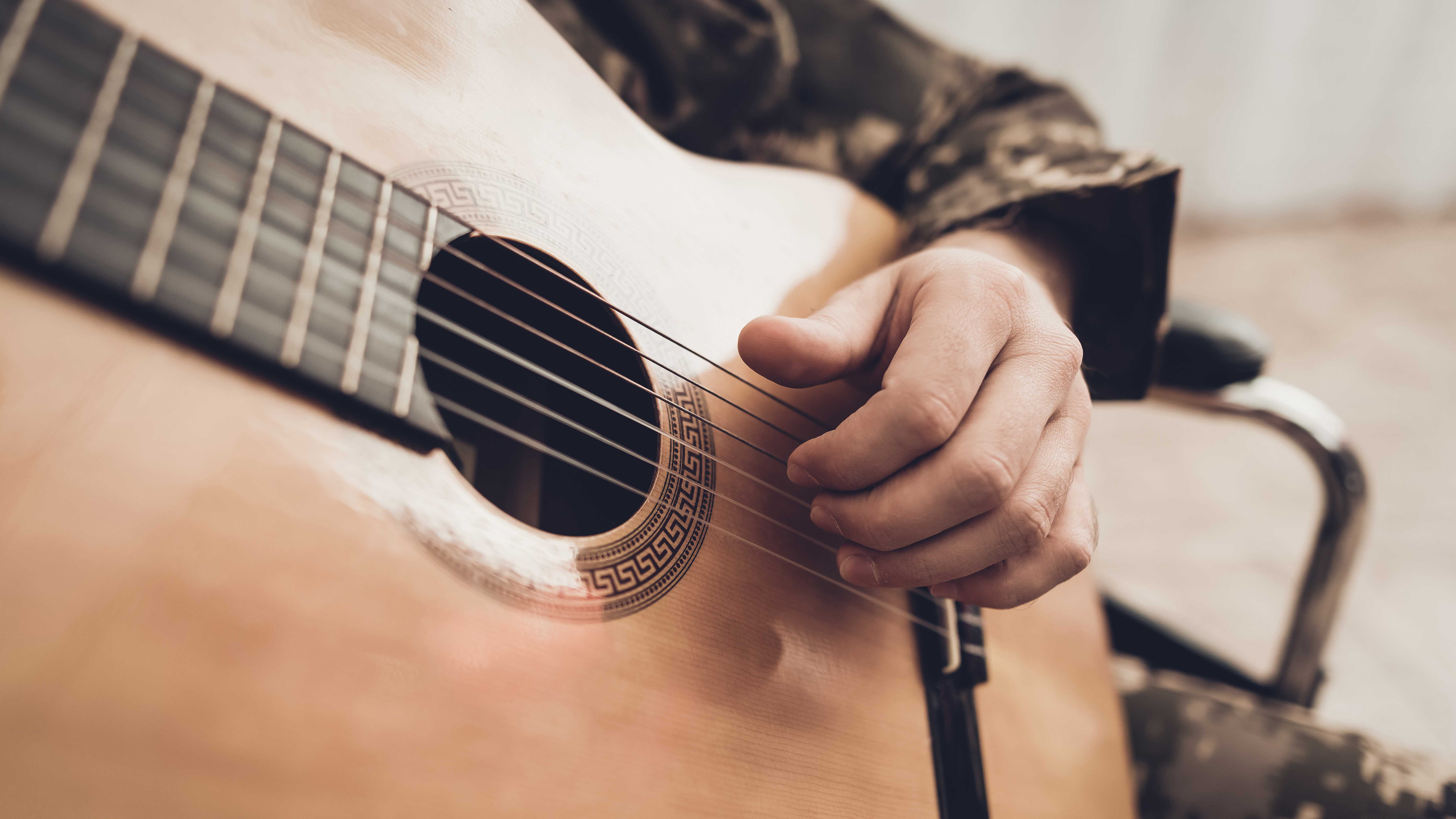 A soldier in fatigues plays a guitar