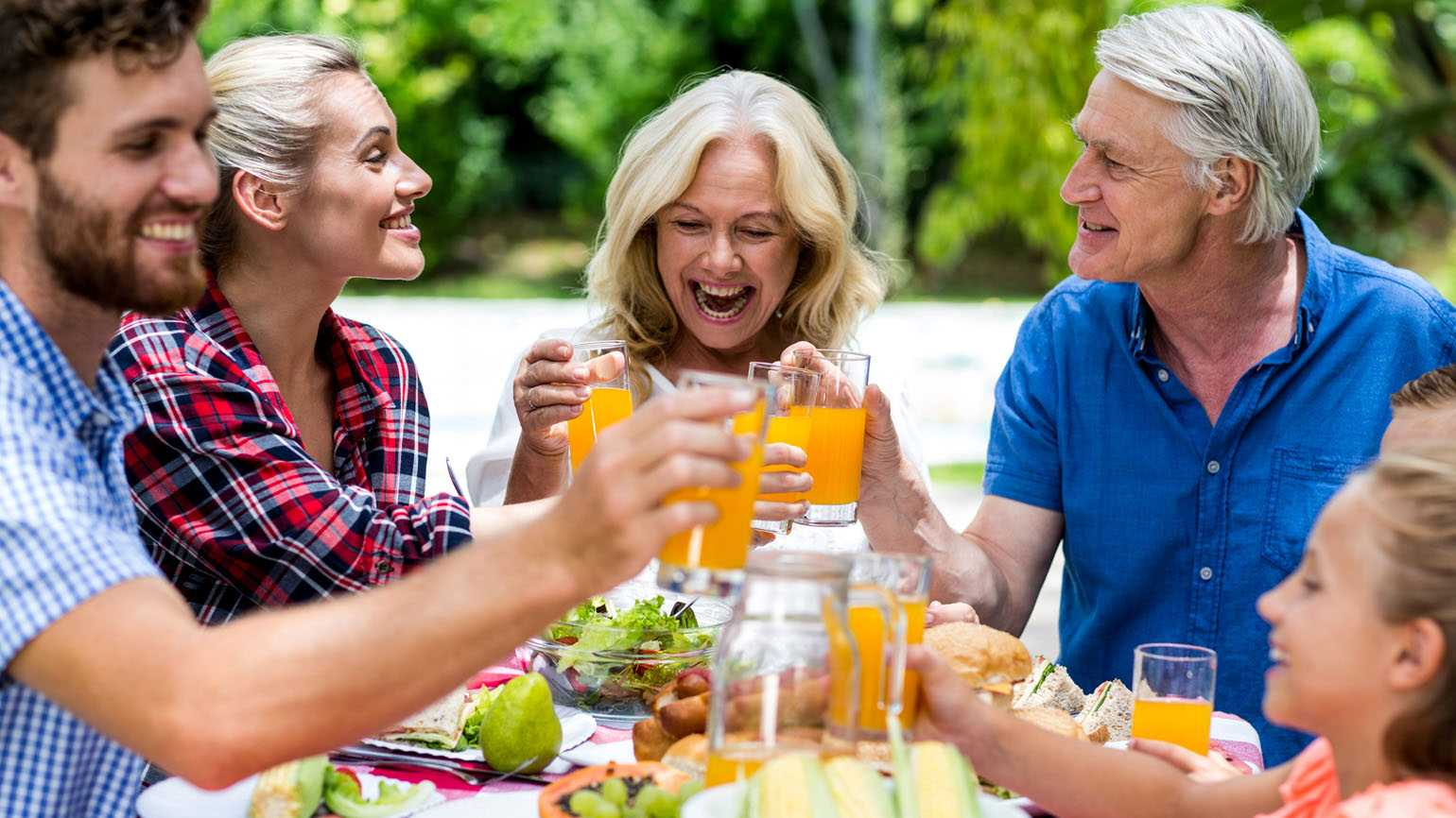 A family enjoying a summer lunch together outdoors.