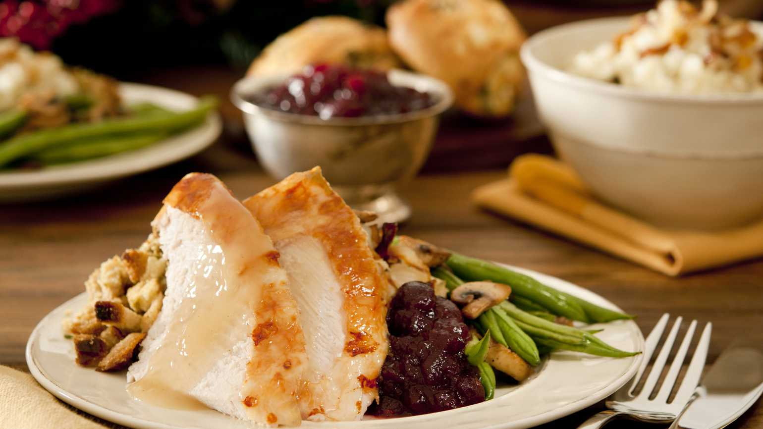 A dinner plate with roasted turkey, string beans, cranberry sauce and stuffing.