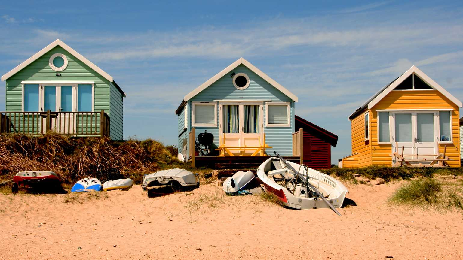 Three colorful beach houses lined up.