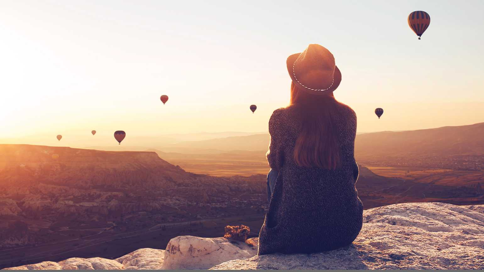 A woman gazes out of hot-air balloons at sunrise