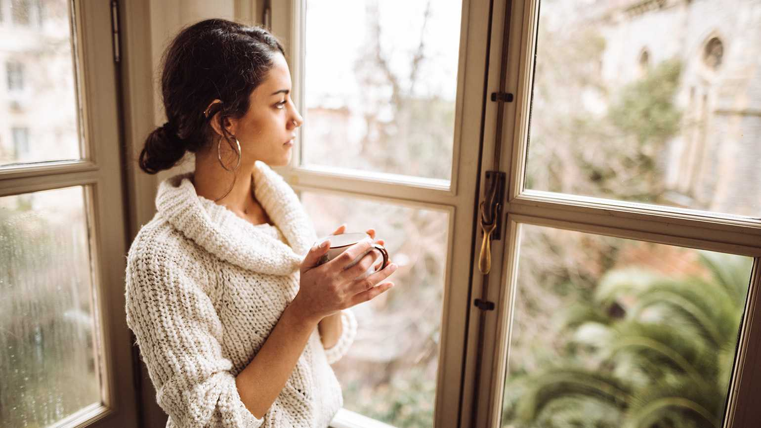 A thoughtful woman gazes out a window