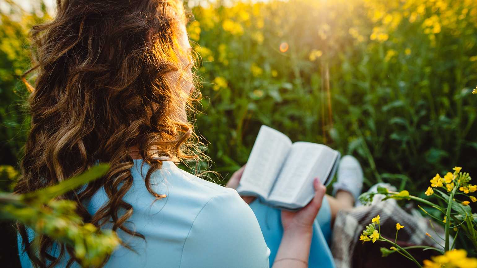 A woman reading the Bible in the grass; Getty Images