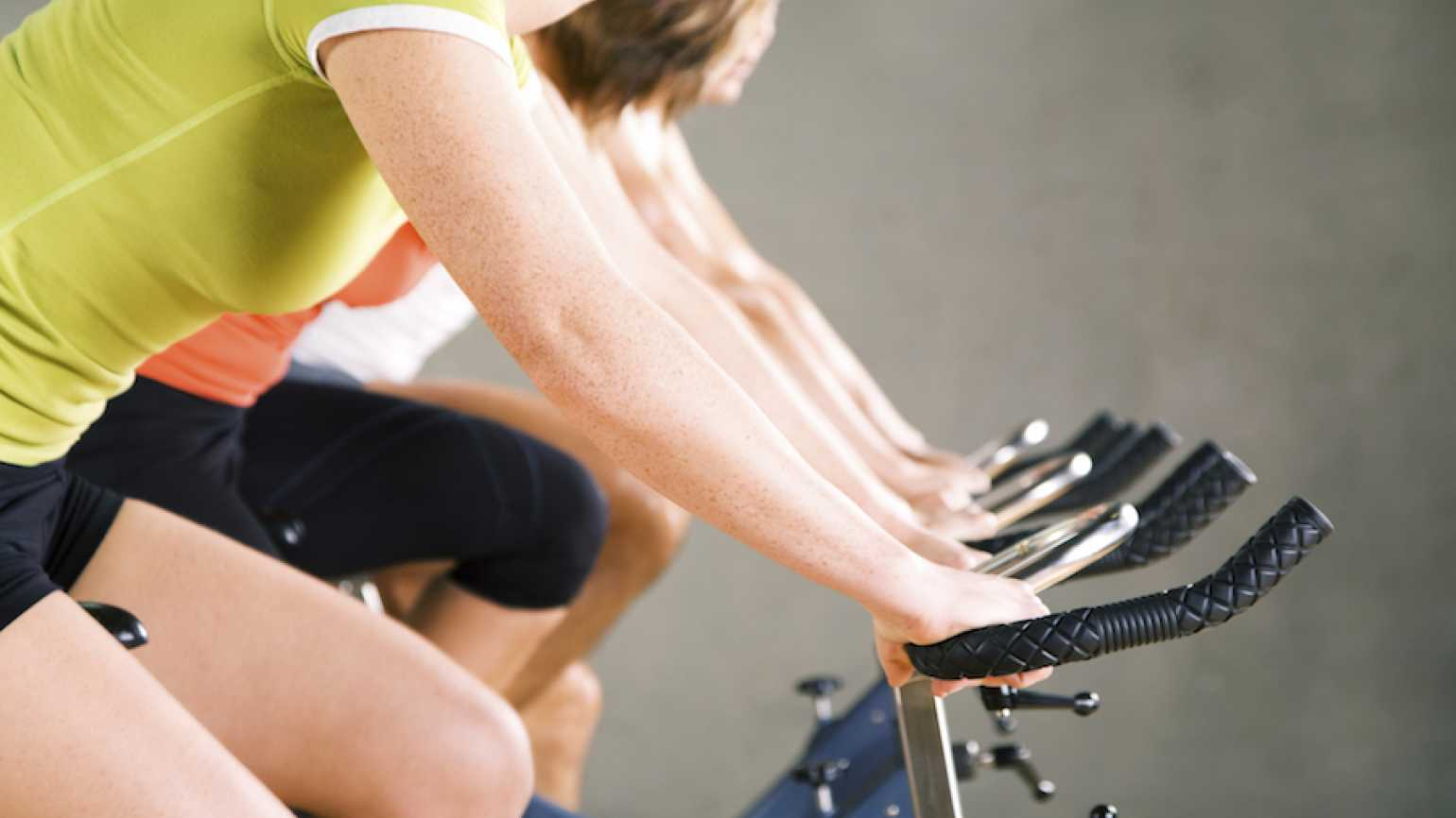 Two sisters support each other at a SoulCycle spinning class.