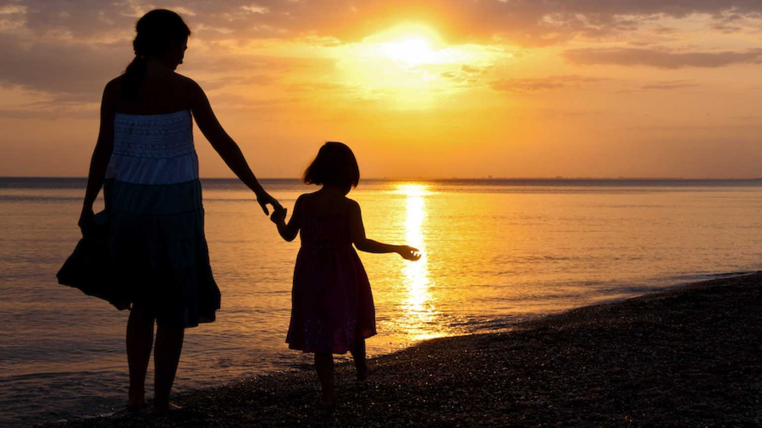 Mother and daughter walking at sunset (Thinkstock)