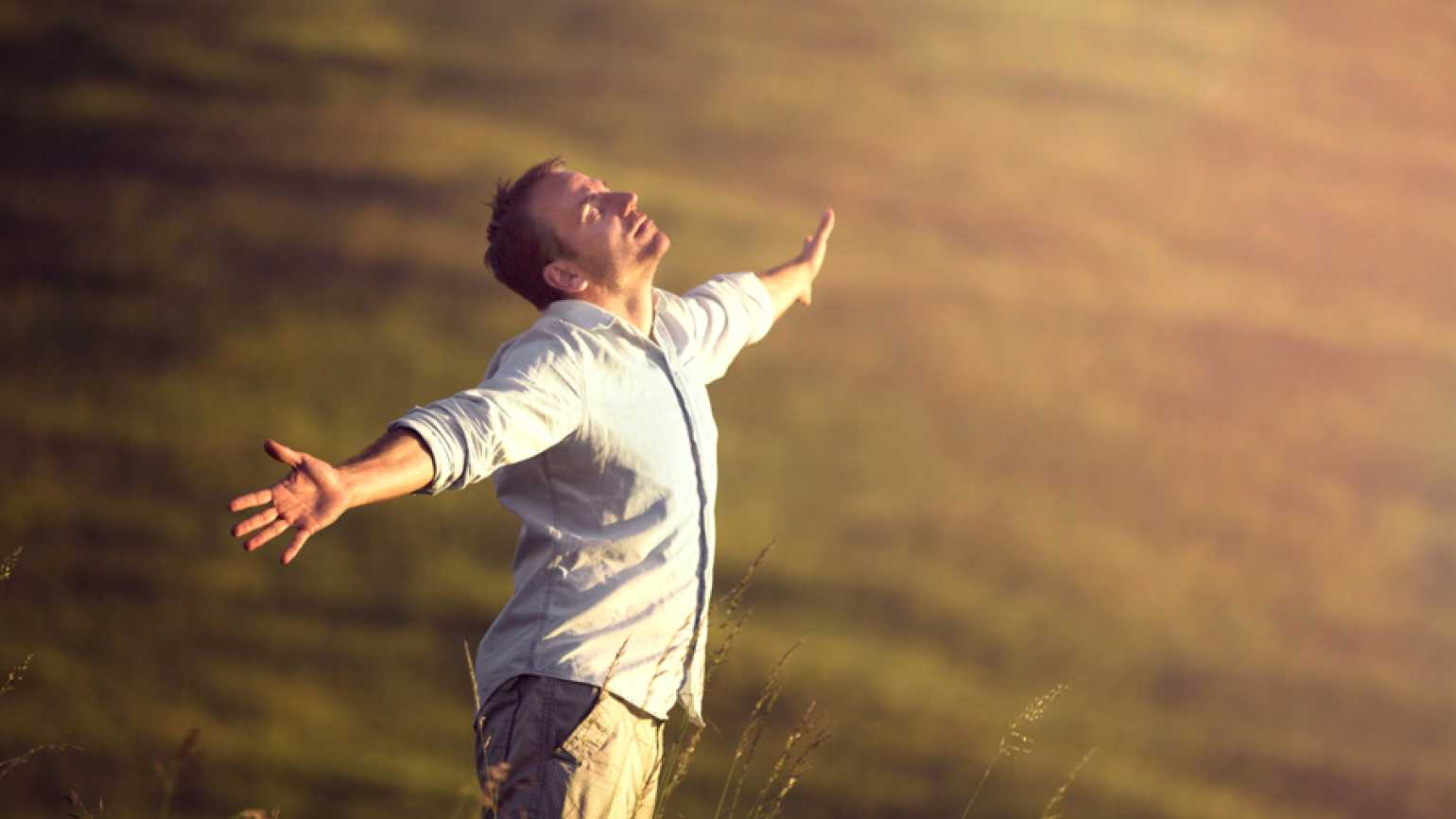 a man looks up to heaven with arms outstretched asking why God