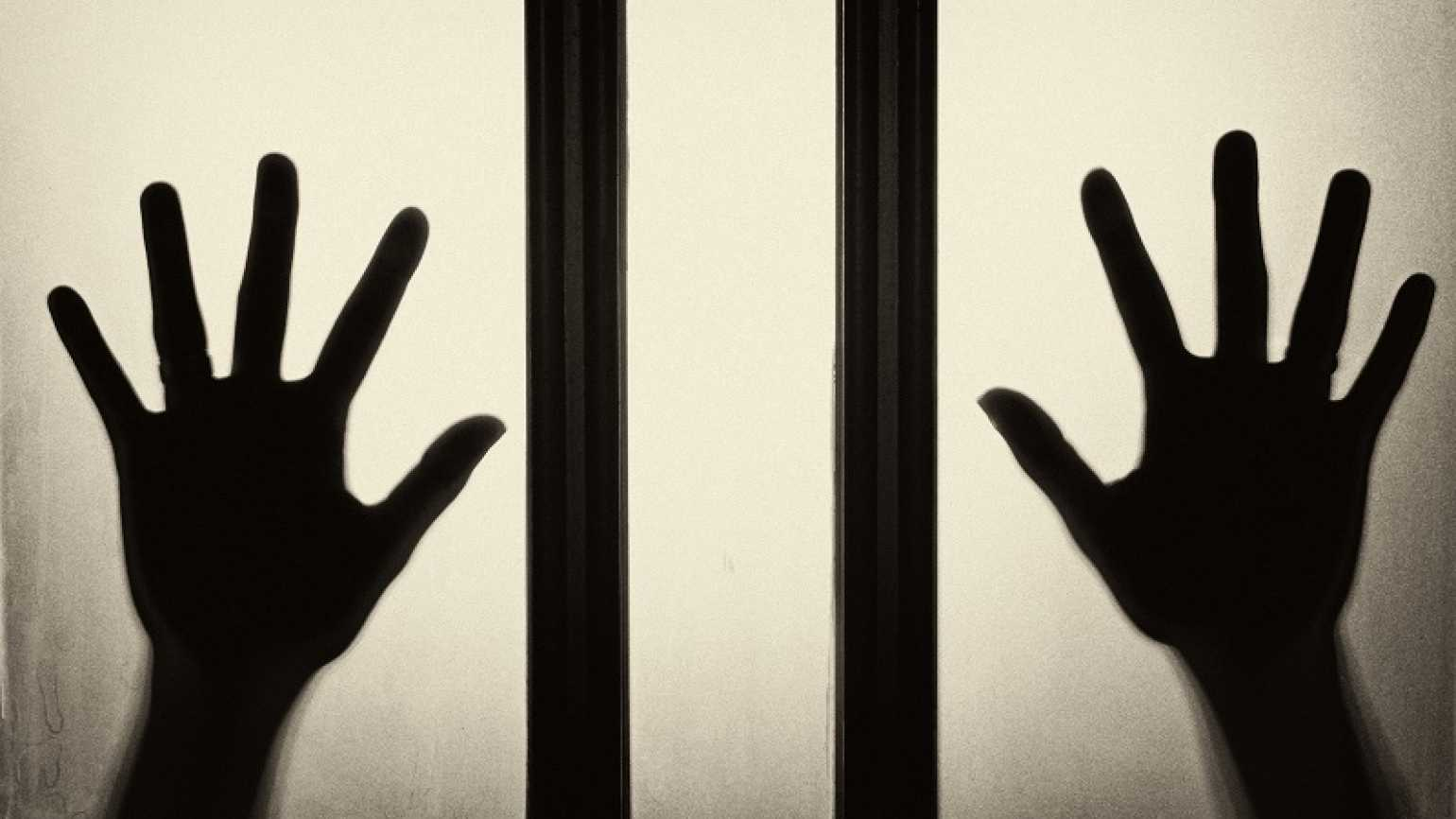 Two hands of a trapped person pressed against glass