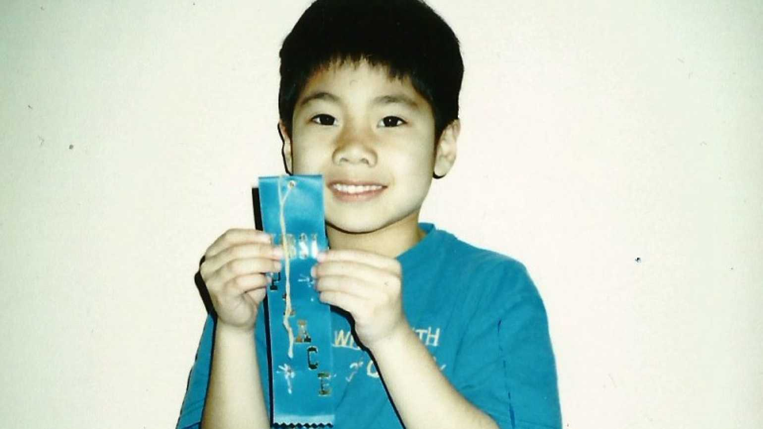 AJ holding the spelling bee first place ribbon