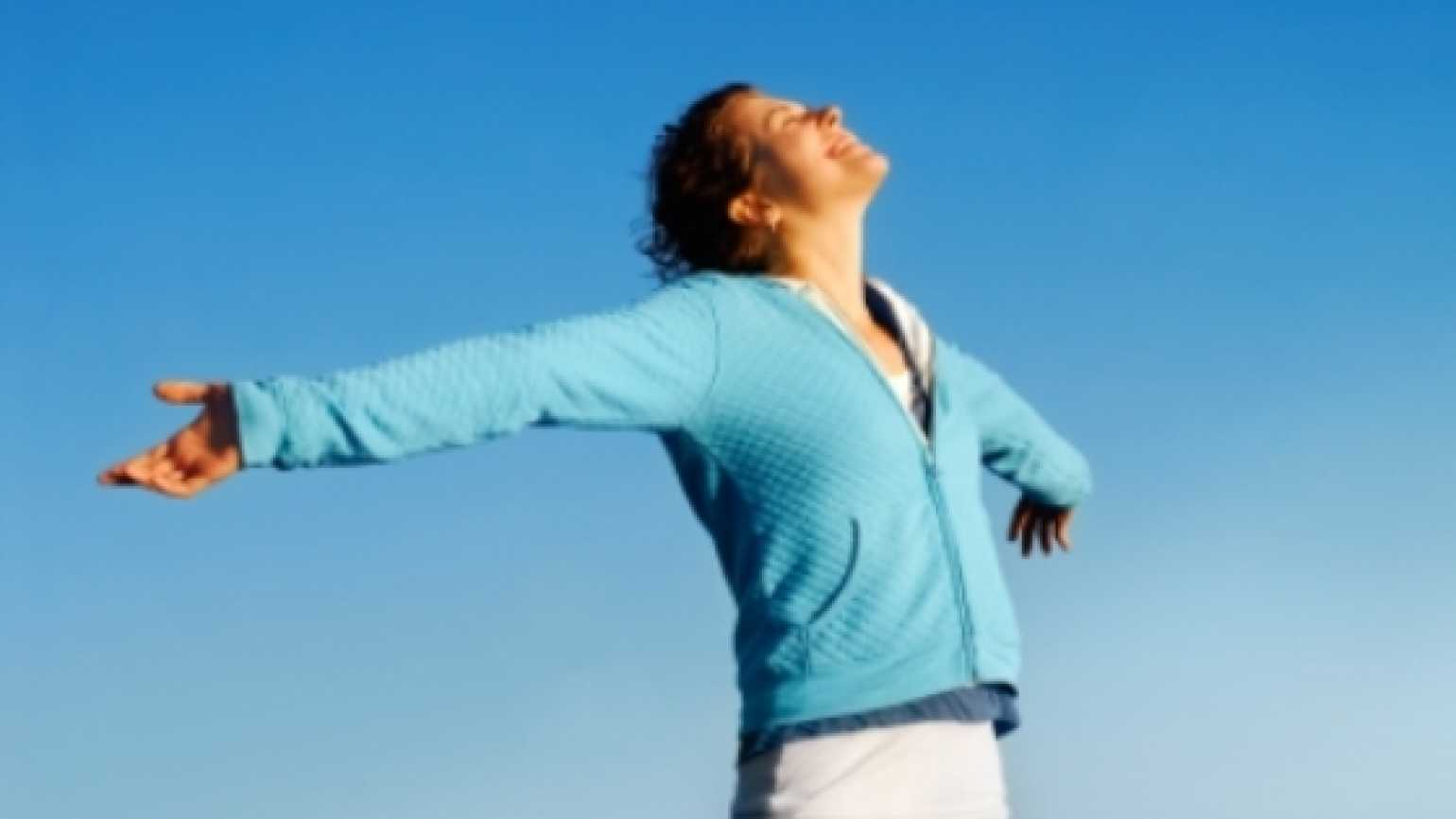 woman with arms outstretched praising God
