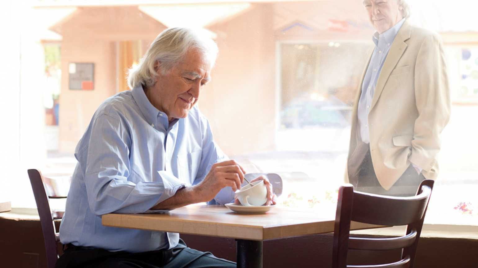 Dr. Larry Dossey gazes through a window at himself, seated in a cafe.