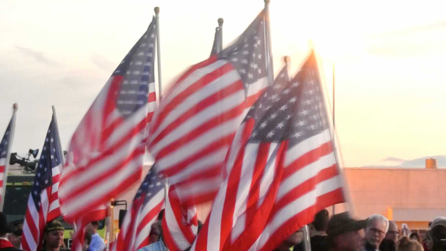 American flags waving in a crowd with sunlight behind them