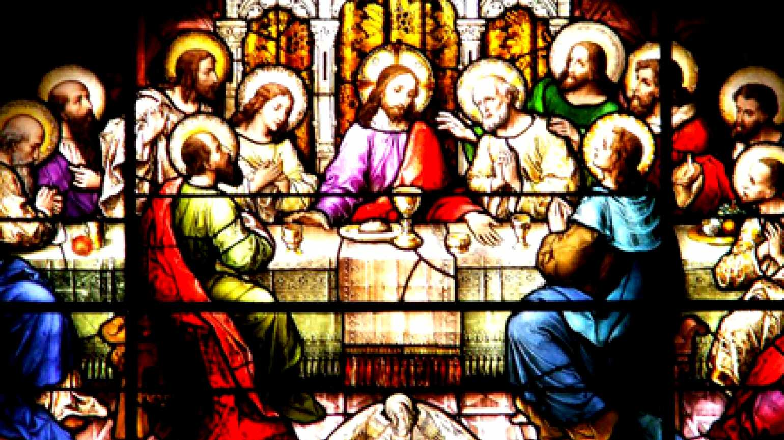 An illuminated stained-glass window showing the Last Supper