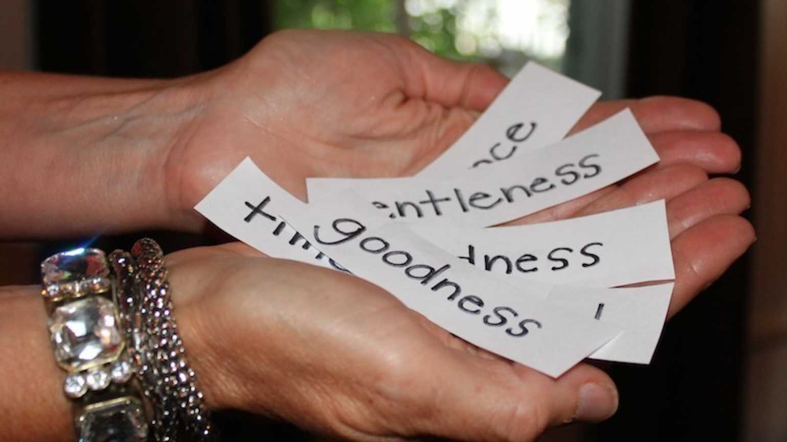 Outstretched hands hold slips of paper that read Goodness, Kindess, etc.