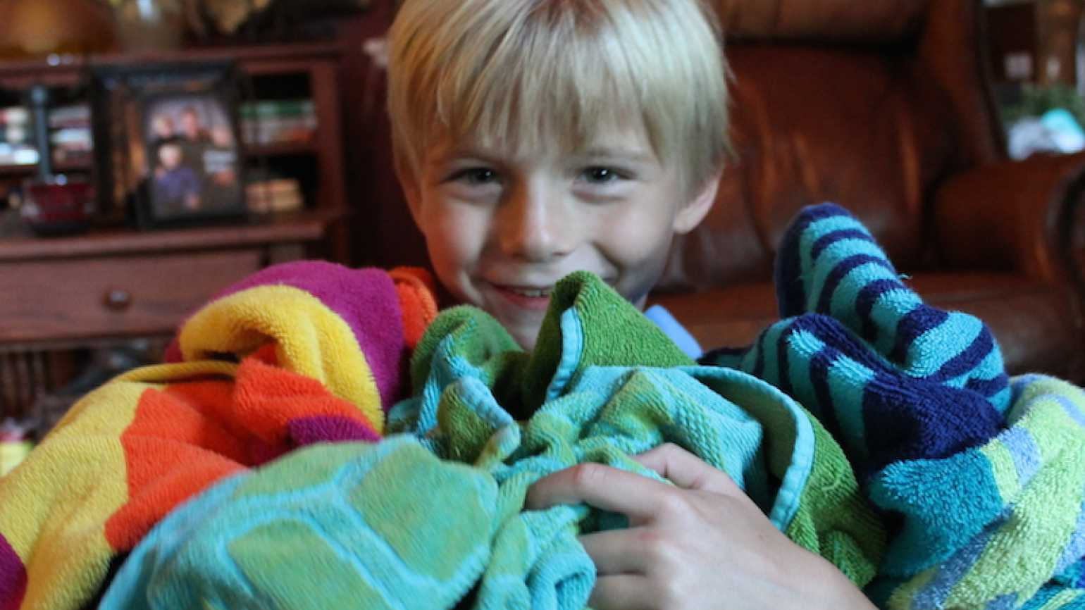 Shawnelle's son Zay holds a jumble of towels.