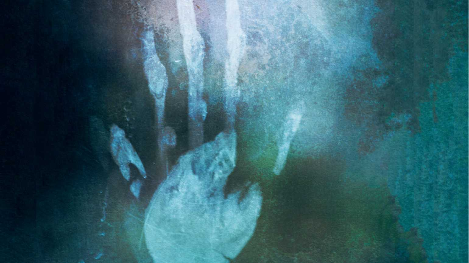 A mysterious hand appears against green-gray of a mirror.