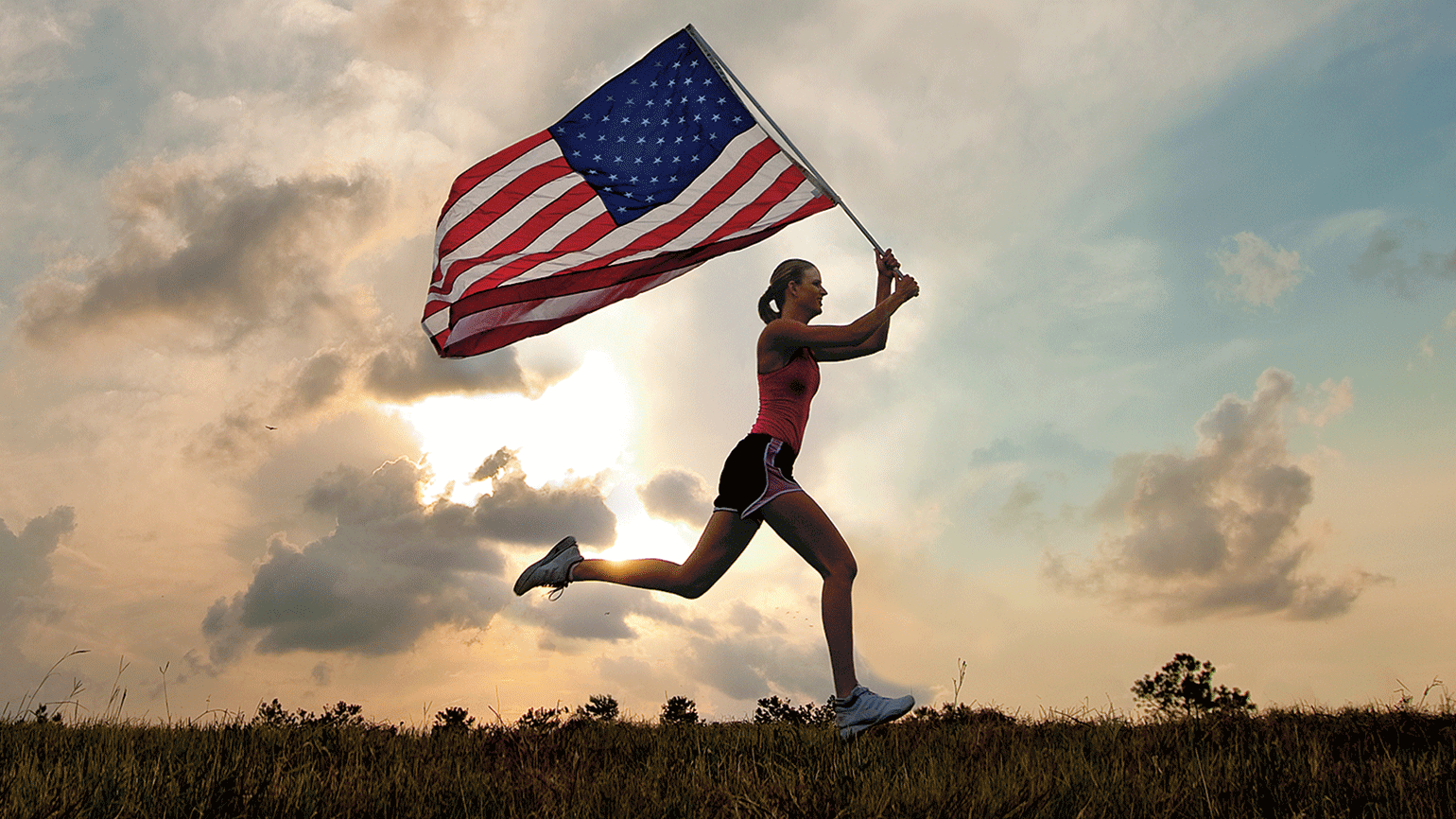 A woman runs at sunrise carrying a large American flag