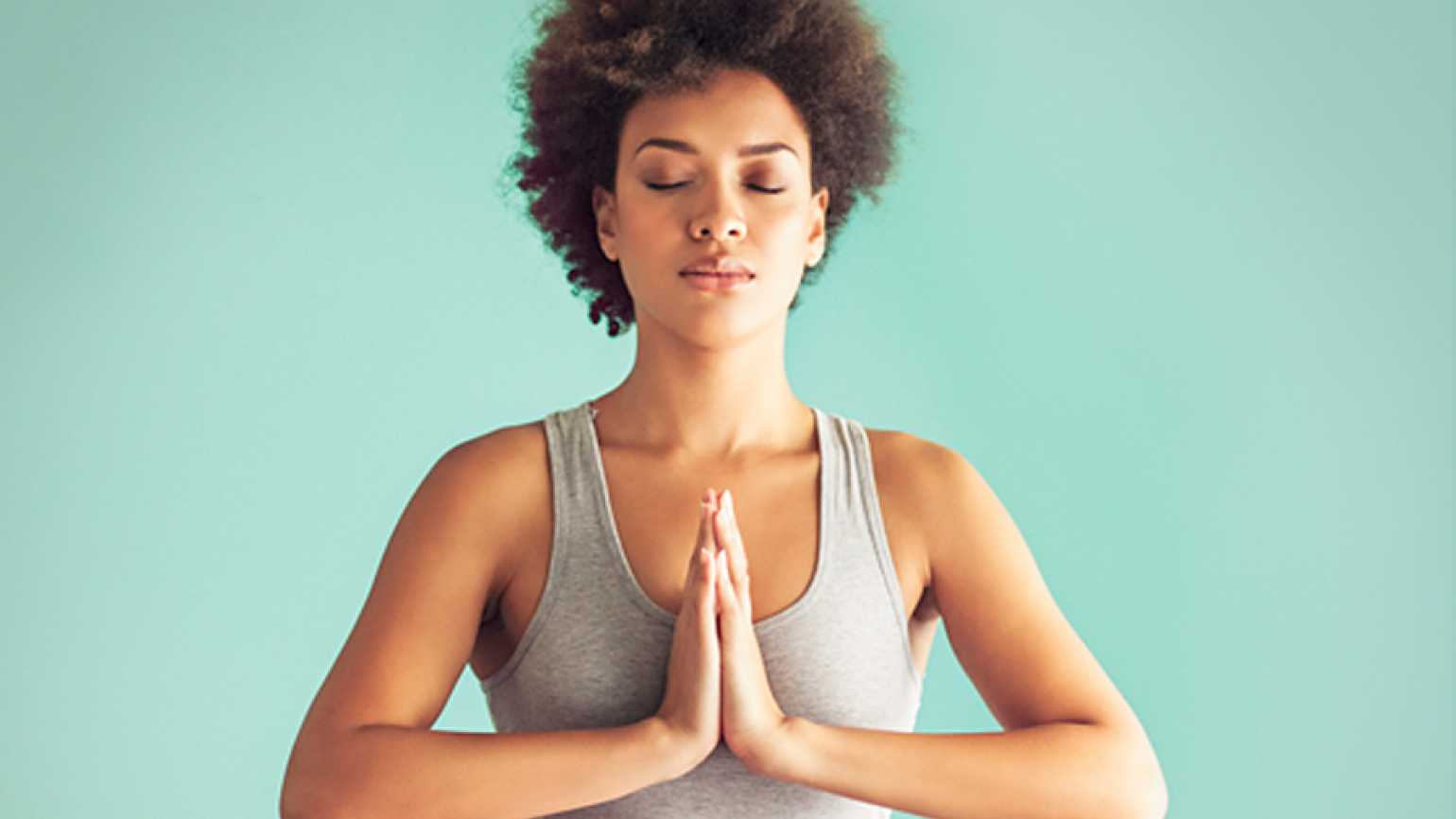 young woman sitting in a yoga pose praying hands