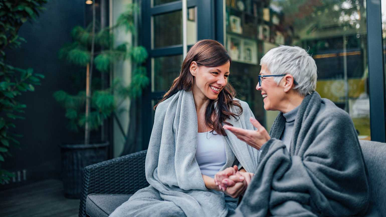 An aging mother having a conversation with her caregiver daughter.