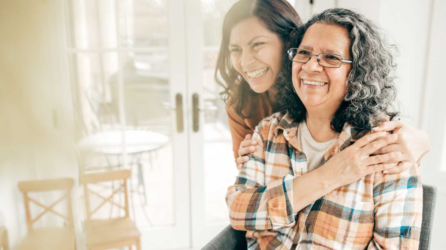A adult daughter with her aging mother in a happy, loving embrace.