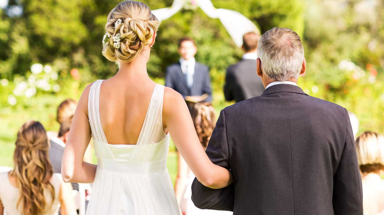 A father walking his daughter down the aisle on her wedding day.