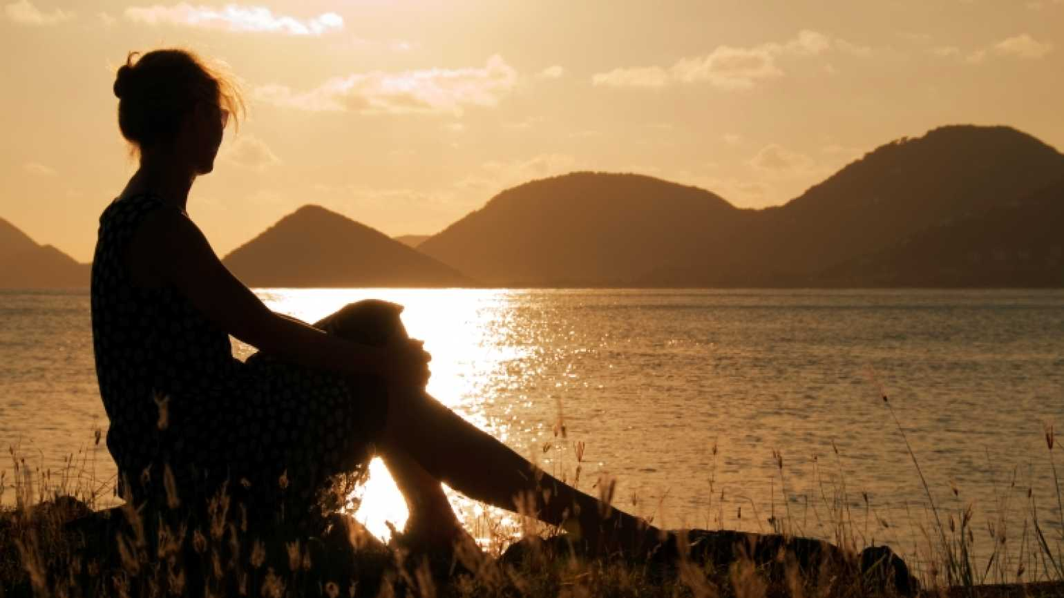 Woman in sunset praying God's promises