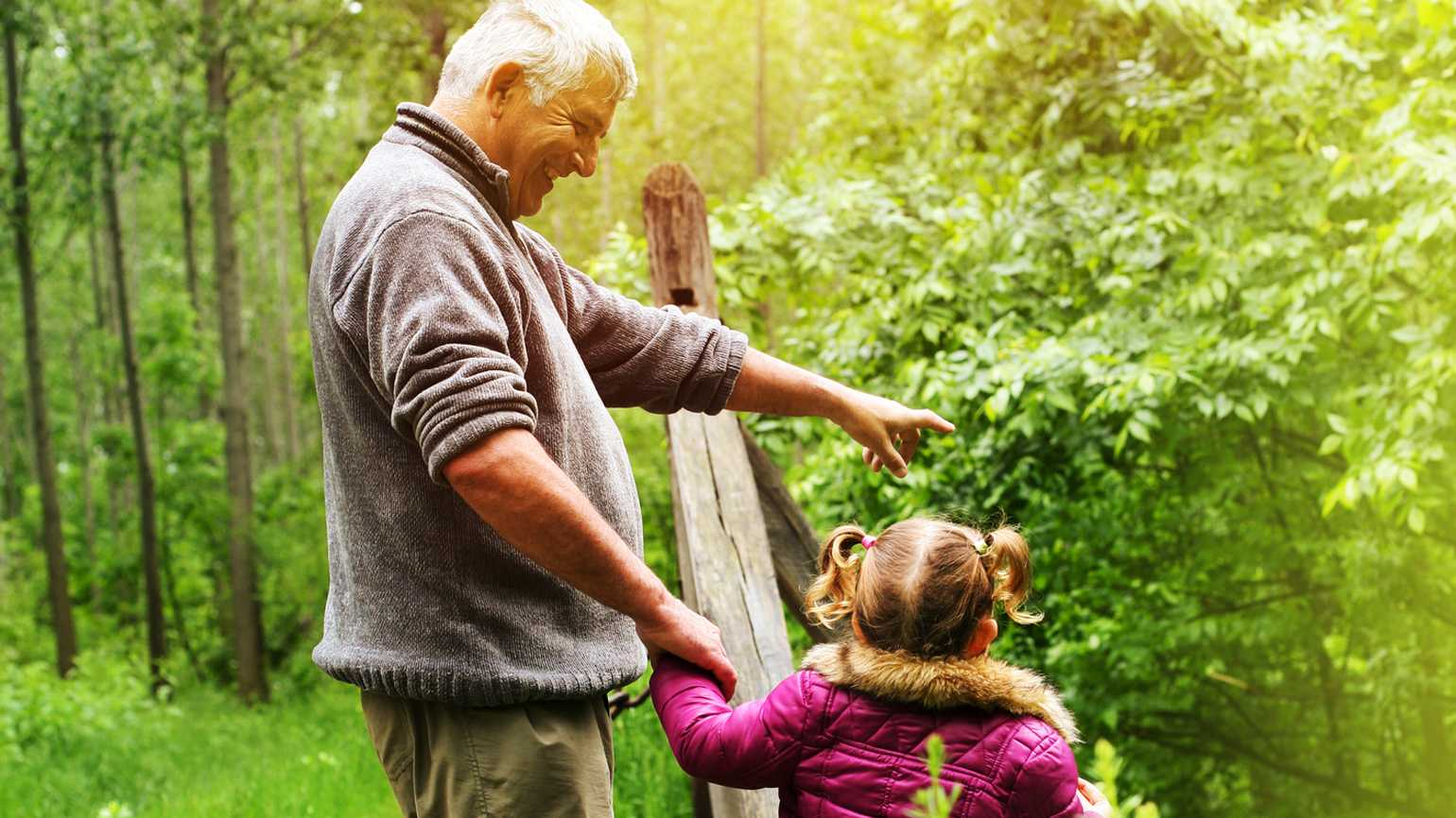 Grandfather showing his granddaughter the woods.