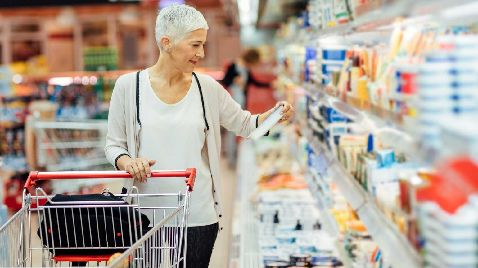 An older woman grocery shopping on a budget.