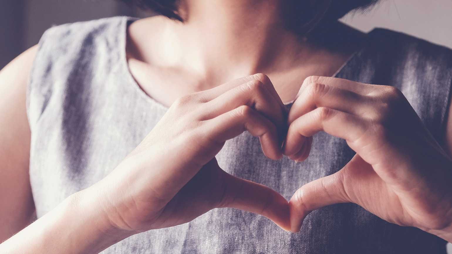 A woman making a heart with her hands; Shutterstock